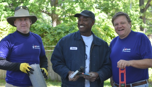 Mr. Kim (center), shown with volunteers, is a contractor partnering with Charis to renovate vacant homes.